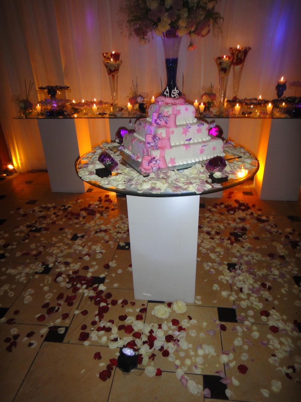 Mesa do bolo. Pétalas jogadas no chão. O efeito ficou bem bonito.
